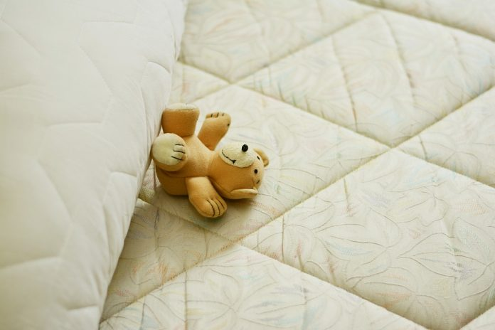 teddy bear on top of the mattress