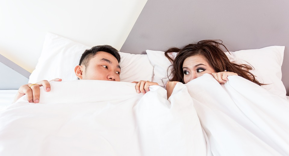 couple laying in the bed covering their body under a comforter due to cold