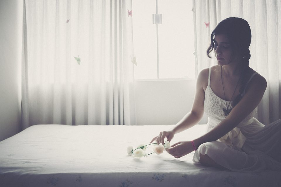 woman sitting on the mattress holding flower crown