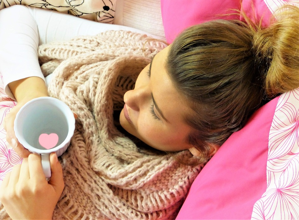 young woman having coffee on the bed